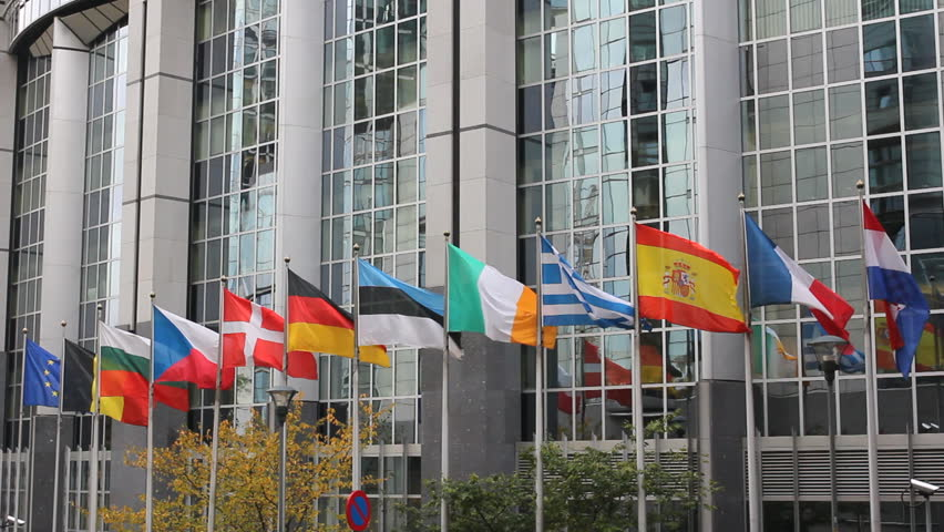 European Union country flags move, reflect on European Parliament building
