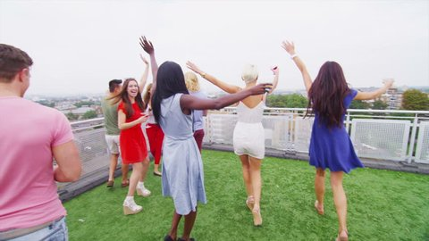 Excited group of young friends enjoying drinks at a party in a London penthouse apartment run out to the terrace to look at the views of the city.