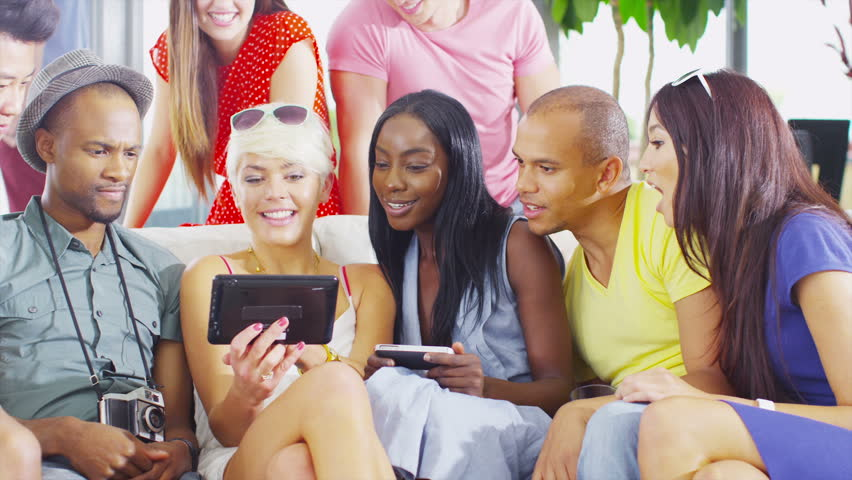 Happy and attractive group of friends hanging out together at home and laughing at what they see on the screen of a computer tablet. In slow motion. | Shutterstock HD Video #5268713