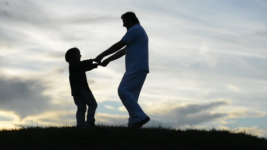 Young father playing with sons on meadow circling them and jumping running for fun