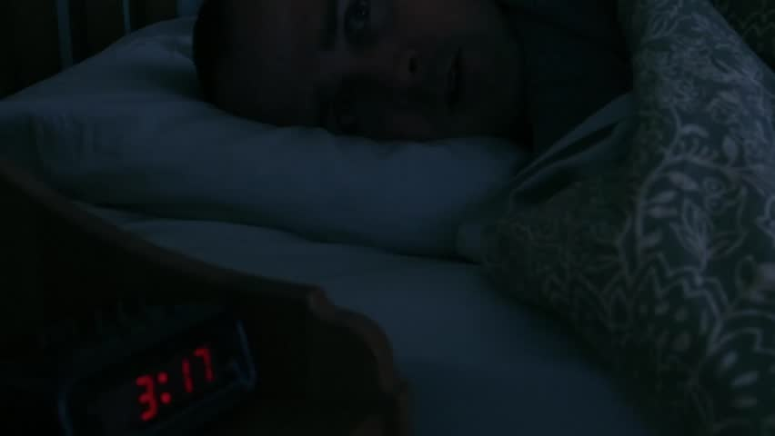 A man with insomnia having trouble sleeping late at night in his bed