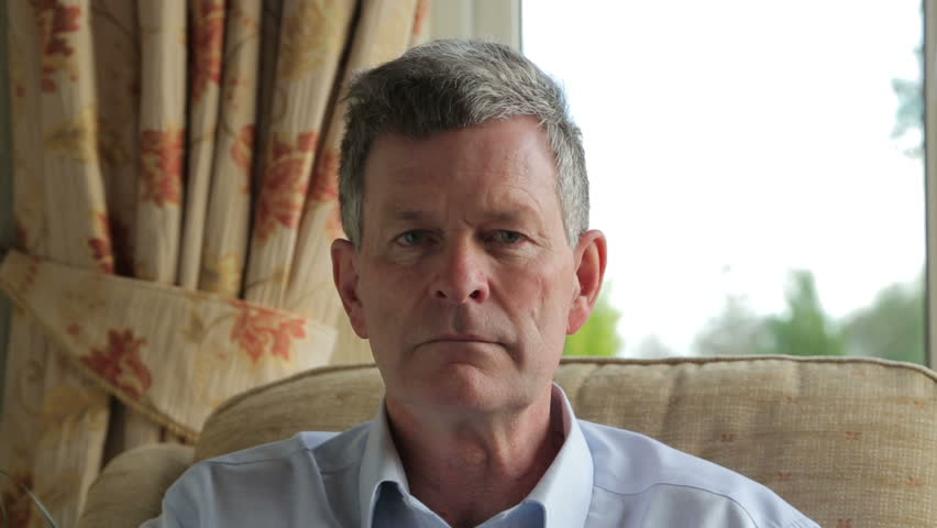 Close up, serious middle aged man turns to camera
