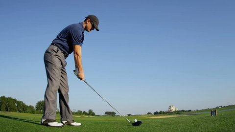 Male Caucasian golfer on green enjoying vacation luxury resort using driver to tee off golf course fairway shot on RED EPIC, 4K, UHD, Ultra HD resolution