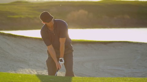 Young male golfer climbing out of course sand bunker after successfully playing the ball shot on RED EPIC, 4K, UHD, Ultra HD resolution