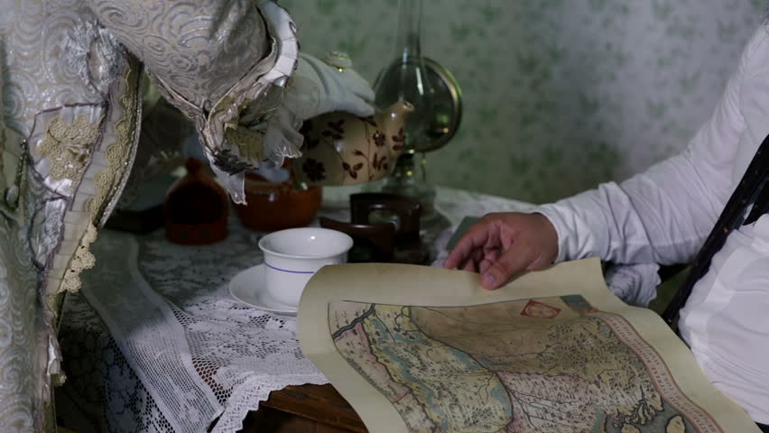 Man getting his cup of tea and looking at an old map