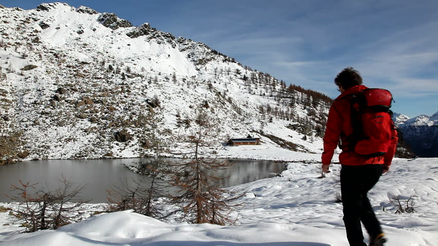 One young male hiker stands in front of a alpine lake looking to the snowy landscape, rear view. Red jacket, black pants. HD1080p Canon 5Dmk2 Buffet Lake, Champorcher, Val d'aosta, Italy, Europe. | Shutterstock HD Video #5364743