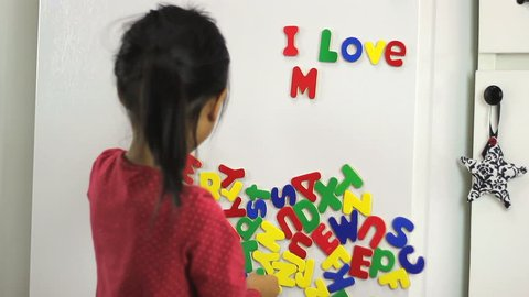 A cute little seven year old Asian girl uses colorful fridge magnet letters to spell I Love Mom on the fridge.