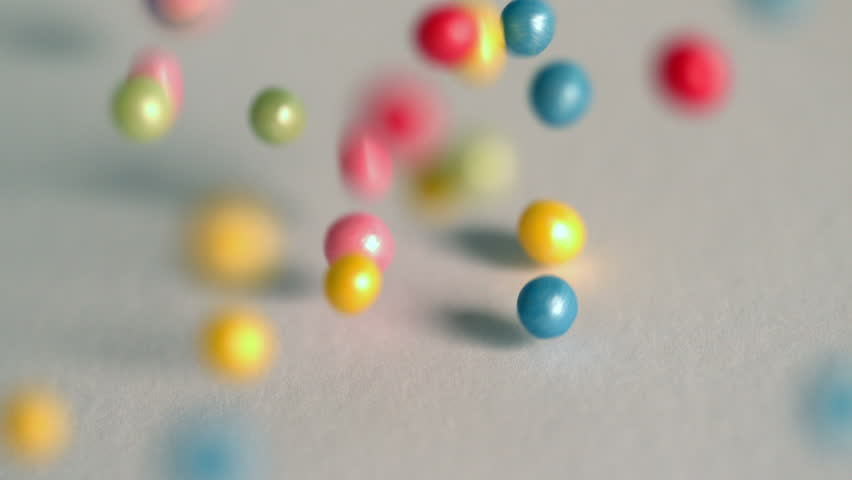 Sugar balls falling onto grey surface in slow motion