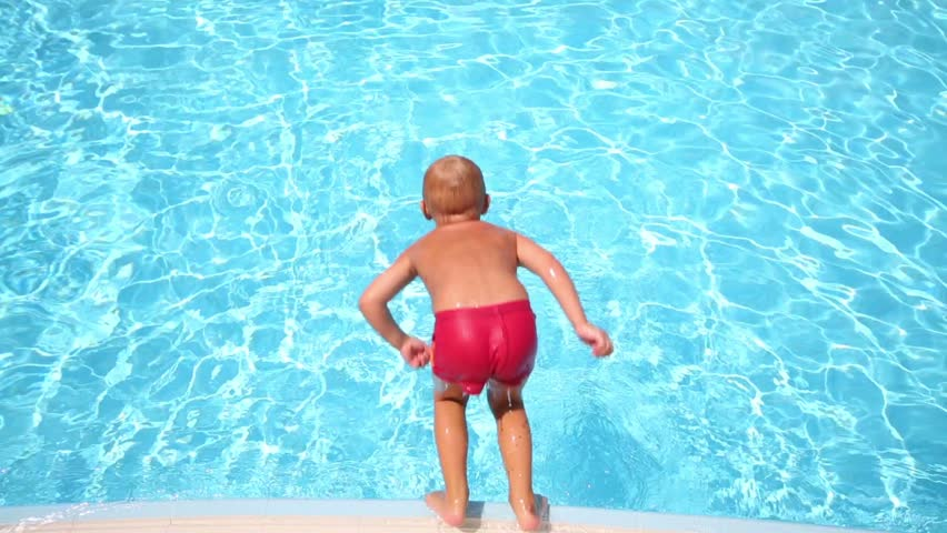 Little boy in red trunks jump in blue pool and swim away