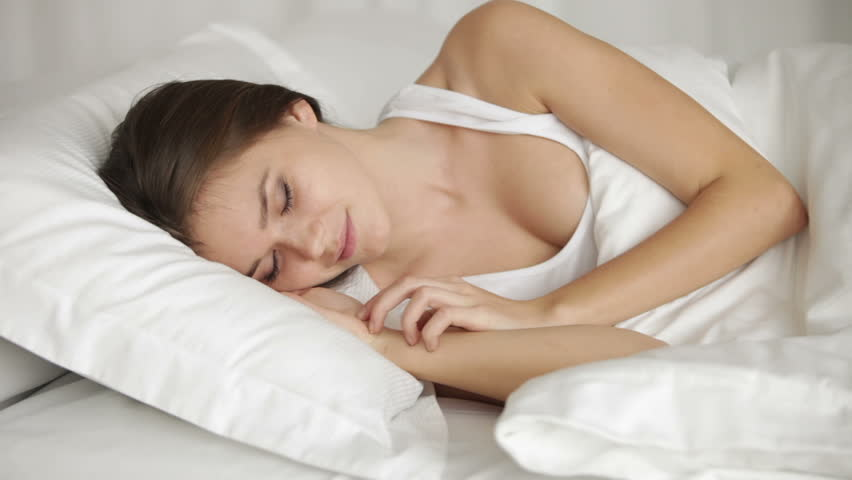 pretty young woman sleeping in bed turning around and smiling in her sleep panning camera