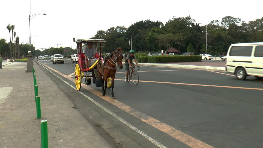 MANILA, PH - JANUARY 22: Horse-drawn carriage, and cars passing a not too busy street front of Rizal park in Manila Philippines on January 22, 2014.