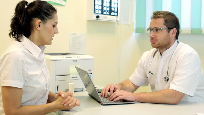 Male doctor explaining something on laptop to young female patient   | Shutterstock HD Video #5488409