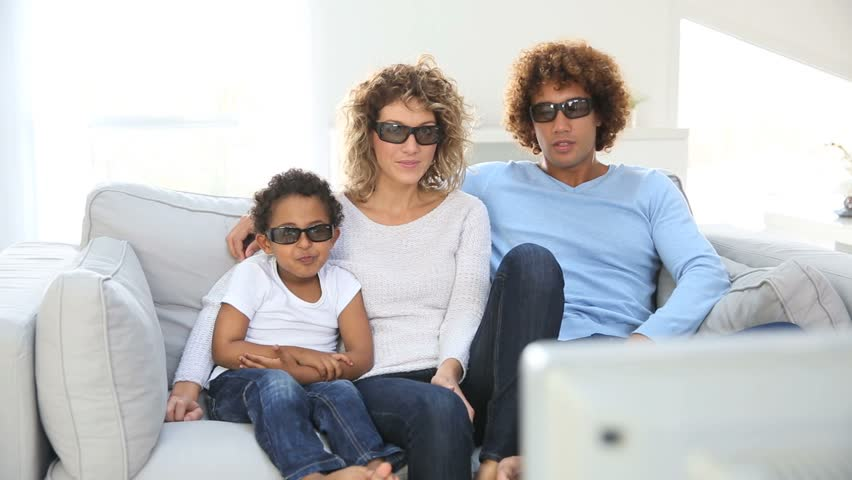 Family watching 3D movie on tv