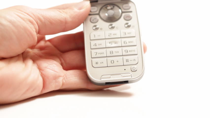 A hand holding a cellular phone, with the other hand making a call, which activates the key back lighting, isolated on white.