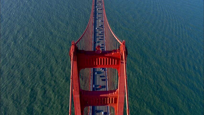 San Francisco Golden Gate Bridge. The scene shows the city of San Francisco. The shot focuses on the traffic on the Golden Gate Bridge. An epic shot traveling above the bridge.