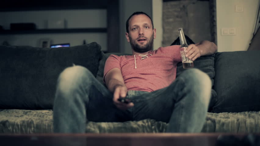 Man watching tv and drinking beer on comfortable sofa