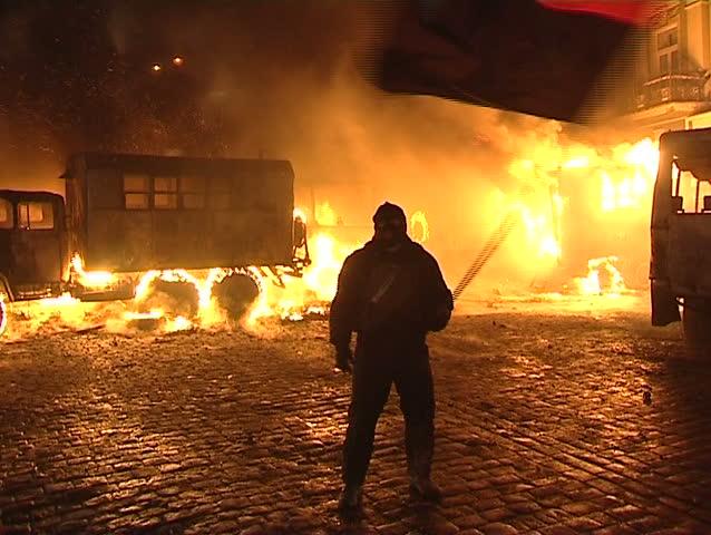 KIEV - JAN 20 2014: 20. January. Ukraine in 2014. Kiev. Burning bus, demonstrators clashed with police. Rebel with a flag
