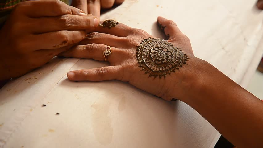 Hand painting using Henna paste at Indian wedding ceremony