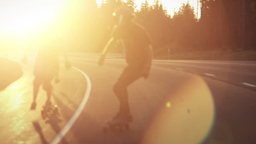 Skateboarders bomb hill during sunset in slowmotion