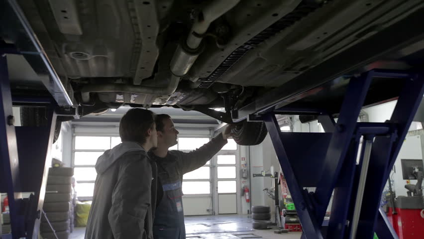 Mechanic and the car owner stand under the car and debate the issues | Shutterstock HD Video #5568716