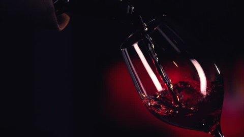 Red Wine Pouring into Glass. Black Background. Slow Motion Shot 240fps