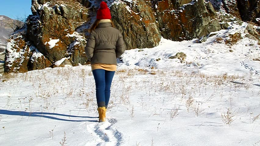 Young girl goes through the snow to the rock