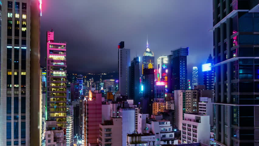 City Night Timelapse.  Wide Zoom In. Attractive Hong Kong night timelapse. Commercial office buildings, commercial LED flashing billboards and residential buildings. Fast moving cloud on the sky.