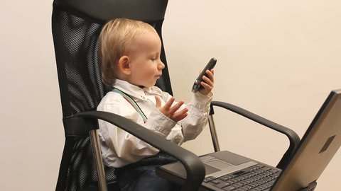 Cute baby play businessman at office, concentrated at work
