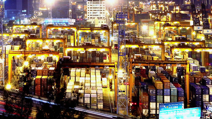 Containers Port Timelapse at Night. Hong Kong. Tight Shot. Cargo containers loading activities in cargo terminal.  Busy traffic across the main road at rush hour. Corporate buildings at the back.
