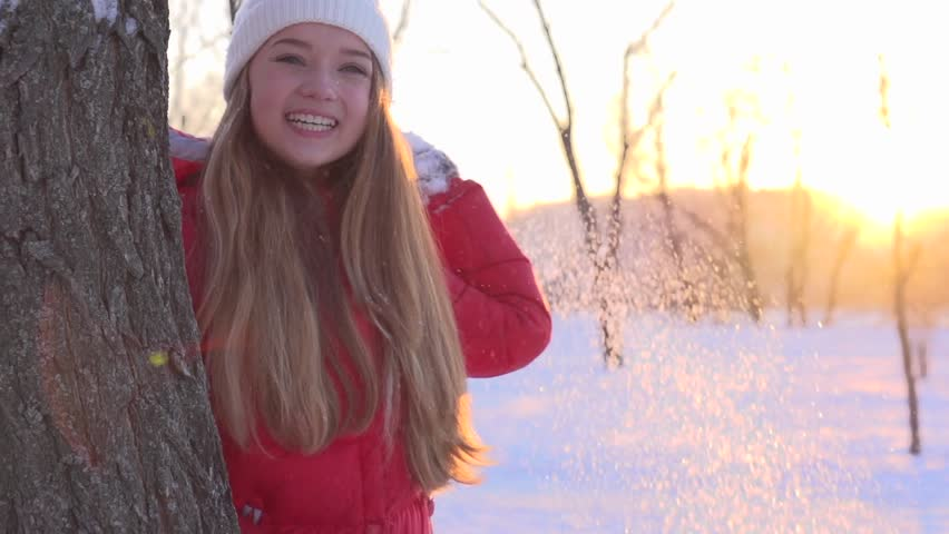 Winter Joyful Girl Throwing Snow. Happiness. Young Woman throwing a snowball outdoors. Laughing People having fun in sunny winter park. Slow motion video footage 240fps. Slowmo