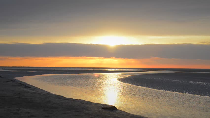 Colorful sunset over the beach at the island of Schiermonnikoog in the North of The Netherlands.   Shutterstock HD Video #5625749