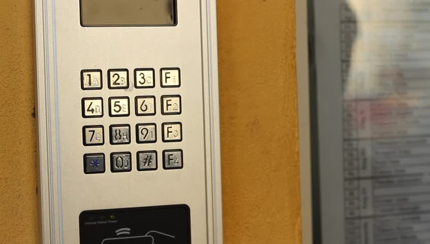 Woman is pressing the keys of an electronic buiding intercom door access device. An intercom, talkback or doorphone is a voice communications system for use within a building