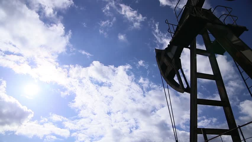 Oil rig pumping over sky. Loop footage.