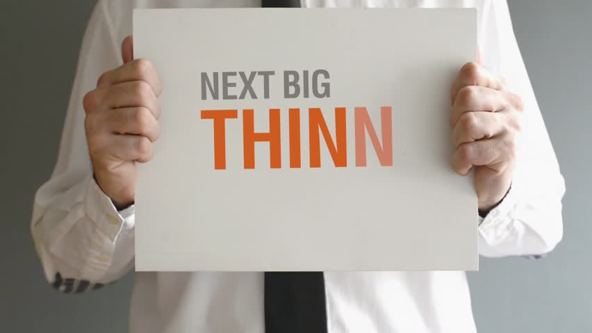 Businessman holding paper board with NEXT BIG THING AHEAD title. Business concept. 1920x1080, 1080p, hd format