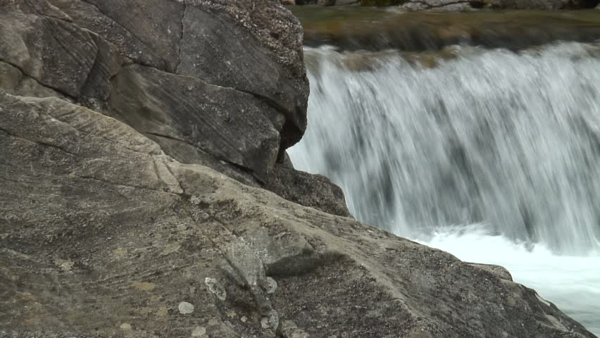 HD 1080i: Close-up of the legs and feets of an mountaineer ascending a rock at a river. Tripod. #57265