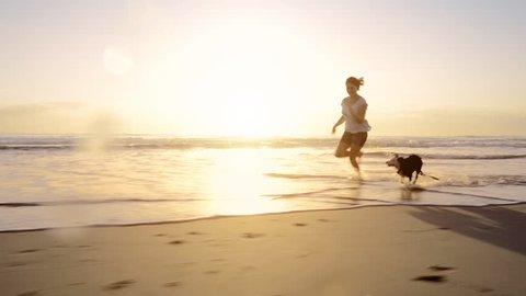 Woman running dog on beach lifestyle steadicam shot