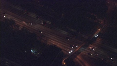 Editorialway cars night. This clip is a wide aerial shot of cars on a freeway in Los Angeles, California at night.