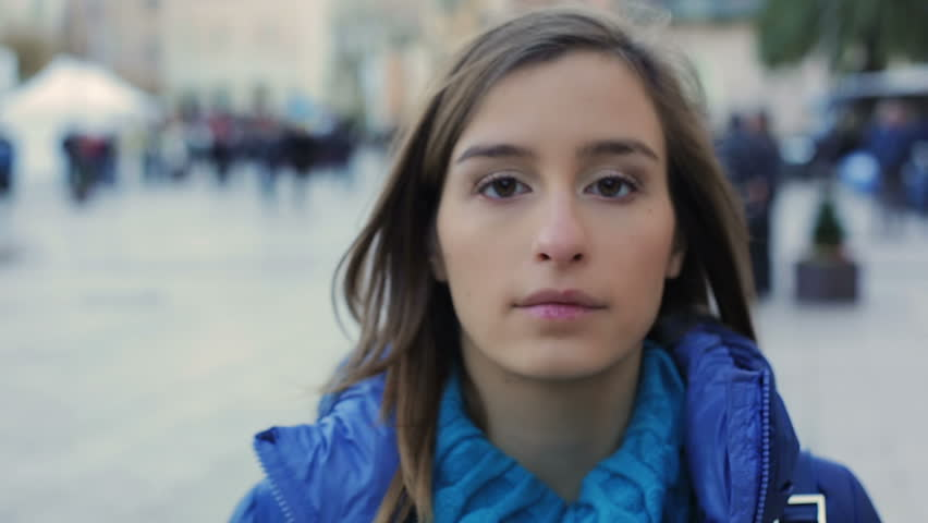 Girl with blue coat in downtown in the evening. She looks at camera. Slow motion