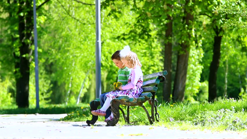 Children Sitting On Bench In Green Sunny Park. Boy With ...