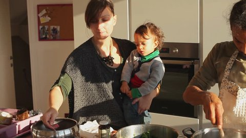multiethnic couple cooking in a spacious kitchen with a kid