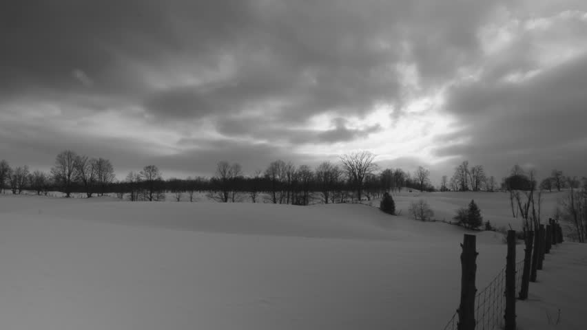 Snowy fields Timelapse. Black and white. Timelapse of sun going down over snow covered fields. Ontario, Canada.