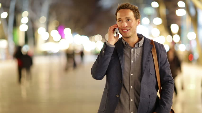 Casual young business talking on smart phone at night on La Rambla in Barcelona. Handsome young business man talking on smartphone and walking towards camera smiling happy wearing suit jacket outdoors | Shutterstock HD Video #5808230
