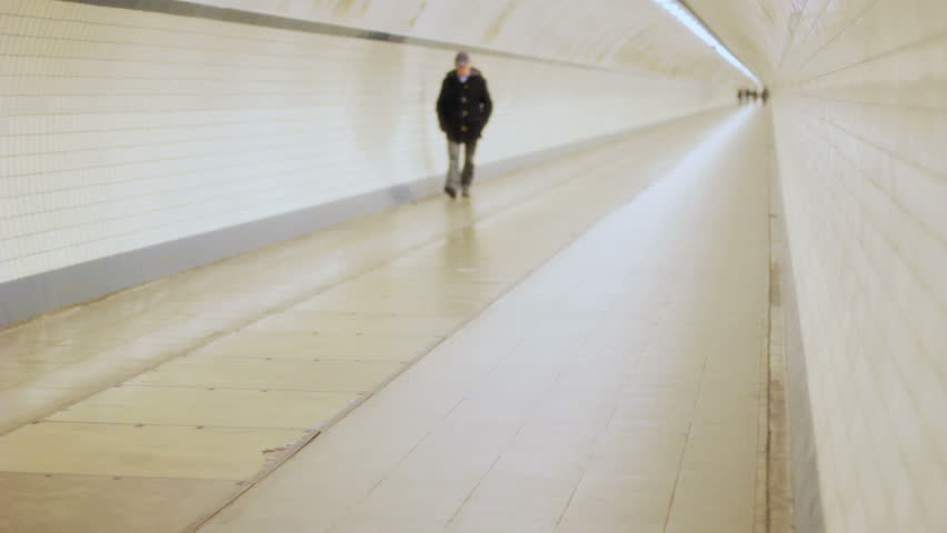 Shallow depth of field slow motion shot of an unrecognizable middle aged man walking alone with a cap on his head and his hands in his pocket in a long pipe shaped tunnel.