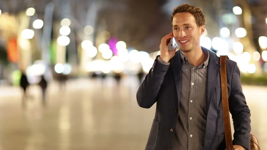 Smart phone man calling on mobile phone at night on La Rambla in Barcelona, Spain. Handsome young business man talking on smartphone and walking away smiling happy wearing suit jacket outdoors.