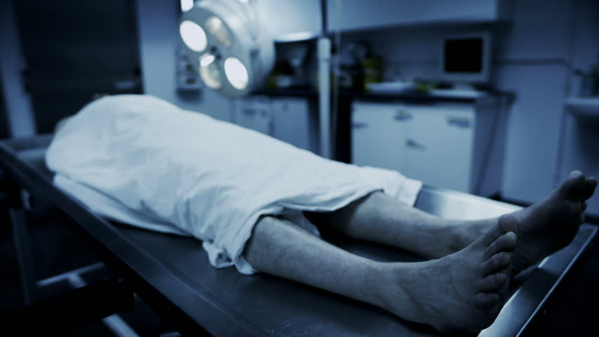 Dead male body laid out on an autopsy table comes back to life