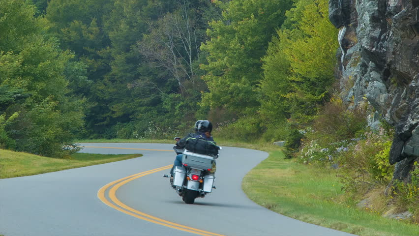 Tourists on a Motorcycle Riding the Blue Ridge Parkway in the Smoky Mountains near Asheville, North Carolina during the Summer with Rock / Stone Walls and Green Trees Around them. Sound Included.