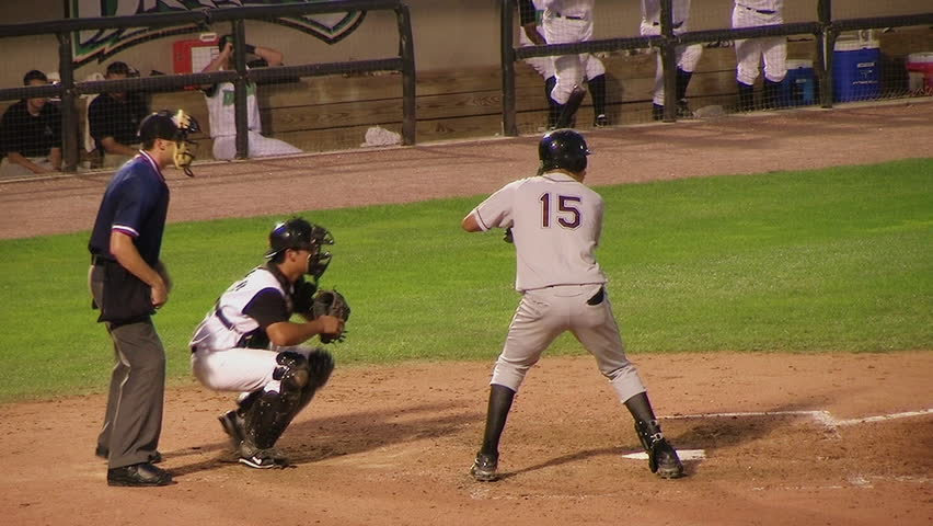 Batter hitting baseball.