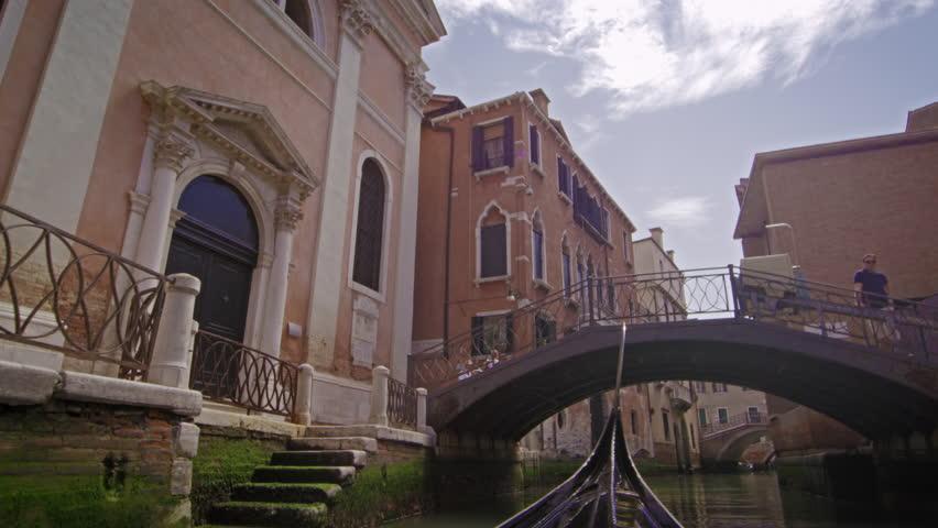VENICE, ITALY - MAY 2, 2012: Slow motion shot of gondola under bridge