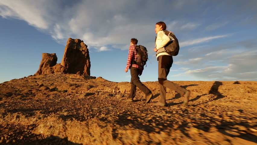 Hiking people - hiker couple at sunset in beautiful landscape. Hikers man and woman trekking walking with backpacks in trail at sunset in mountains by Roque Nublo, Gran Canaria, Canary Islands, Spain.   Shutterstock HD Video #5838299
