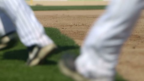A team of baseball players run from the field toward the dugout in slow motion.